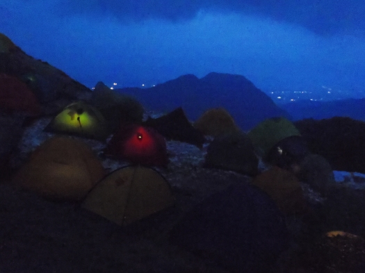 Returning to camp---headlamps in tents, and the lights of the city beyond.